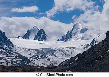 Snow-capped mountain peaks under the clouds