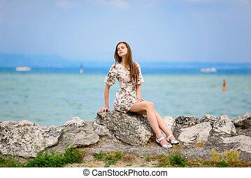 Beautiful woman  sitting on rock over sea