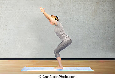 woman making yoga in chair pose on mat