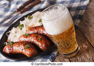 Lager beer and sauerkraut with sausage close-up. horizontal...