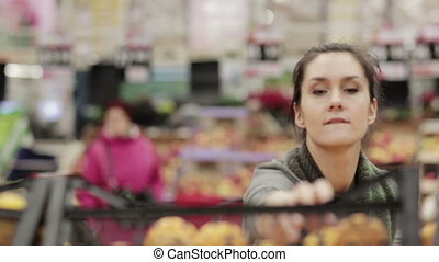 Young woman chooses ripe oranges on store shelves. - Young...