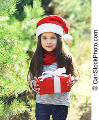 Christmas child in santa red hat with gift box
