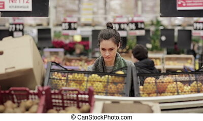 Young woman chooses ripe oranges on store shelves - Young...
