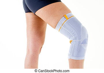 Woman Wearing Flexible Knee Brace in White Studio - Close Up...