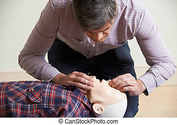 Man In First Aid Class Performing Mouth To Mouth...