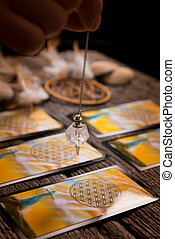 Hand with pendulum over tarot cards - Fortune teller holding...
