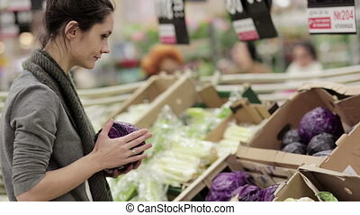 Young woman chooses cabbage on store shelves - Young...