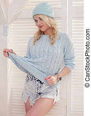 sexy blonde woman wearing shorts sweater and hat on white
