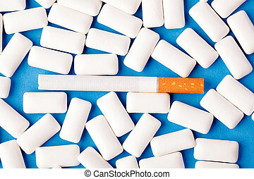 chewing gums and cigarette on blue background