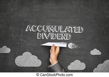 Accumulated dividend concept on blackboard with paper plane...