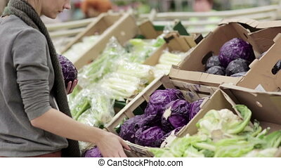 Young woman chooses cabbage on store shelves.