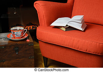 Books on armchair with cup of the by the fireplace - Books...