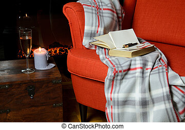 Blanket, books, notepad and pen on armchair with wine,...