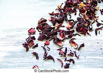 dry red tea leaves on wooden background