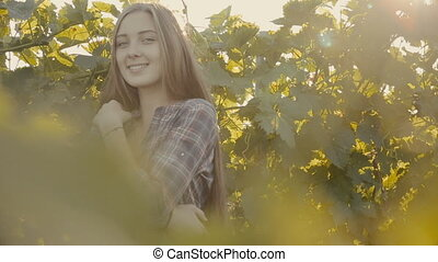 Attractive young woman posing next to the vine