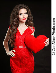 Beuatiful girl with Valentine heart wearing in red dress isolated on black background. Beauty Fashion Portrait. Manicured nails