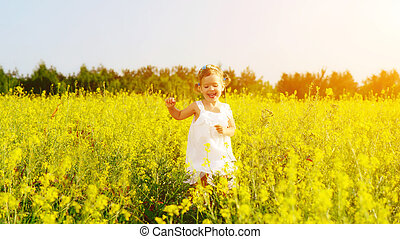happy little child girl running on field with yellow flowers