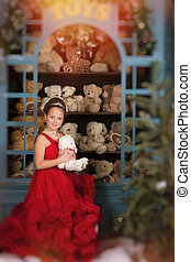Girl in a red dress hugging a teddy bear - Adorable little...