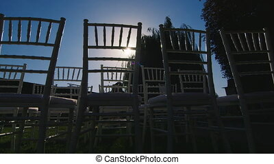 The sun shines through the row of chairs