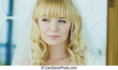 Young attractive bride looks in the mirror. She has blonde hair and blue eyes