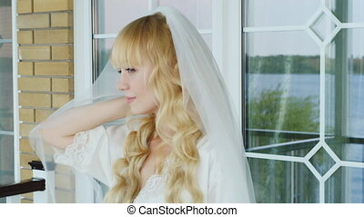 Young attractive bride looks in the mirror She has blonde...