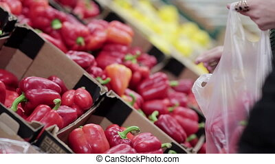 Young woman chooses peppers on store shelves.