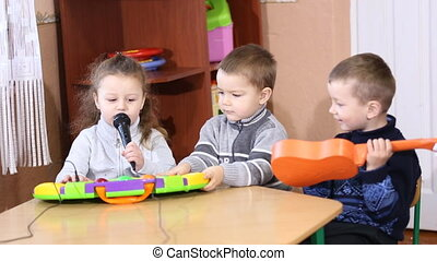 Children playing musical instruments at the table