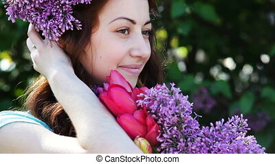 Young woman with lilac wreath Woman with lilac flowers in...