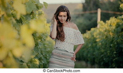Attractive girl walking in the vineyards in the countryside