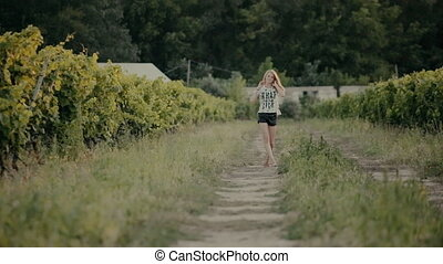 Blonde walks between the rows with grapes grown in the countryside