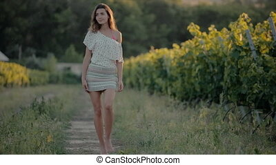 Shy girl goes along the grape rows and blow a kiss