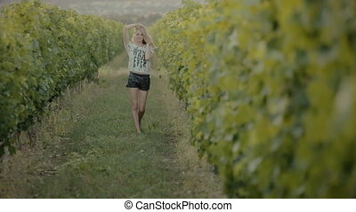 Cheerful girl walks between rows of vines in the countryside...