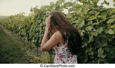 Beautiful brunette going along the rows of vines outside the...