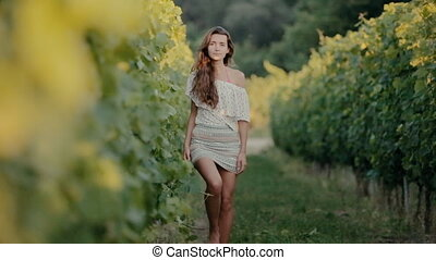 Shy girl goes along the grape rows barefoot