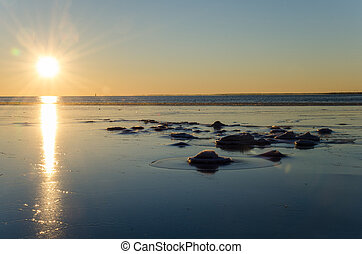 Icy coastal view - Sunlight by an icy and rocky view at the...