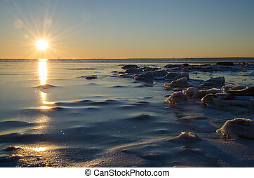 Sunshine at an icy winter coast - Sunlight by an icy and...