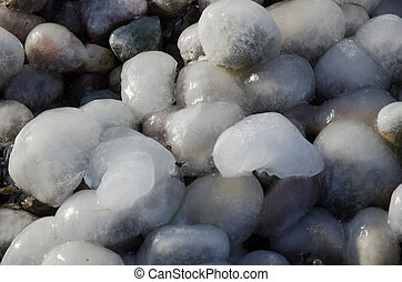 Ice covered pebbles - Detail from a coast with ice covered...