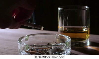Man smokes cigarette and drink alcohol - Man puts out his...