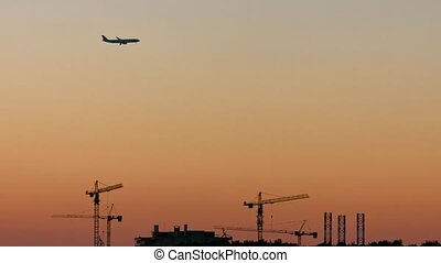Airplane flying at dusk close to construction site