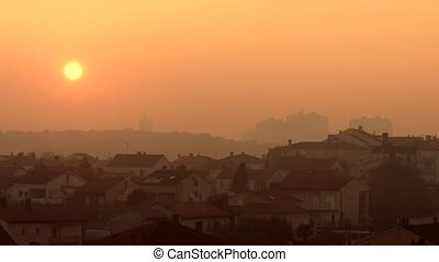 Sunset over village with smoking chimney