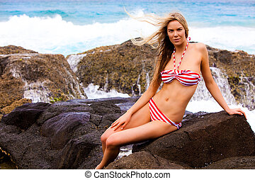 Young Woman in Swimsuit Sitting on Rocks on the Beach