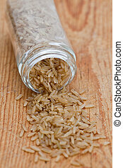 Brown rice in a small glass jar on a wooden background