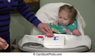 Mom teaches baby how to paint