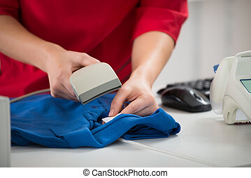 Saleswoman Scanning Barcode On Tshirt - Midsection of...