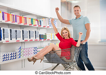 Happy Man Cheering With Woman Sitting In Shopping Cart