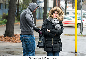 Robber Stealing Clutch From Womans Jacket On Street - Young...