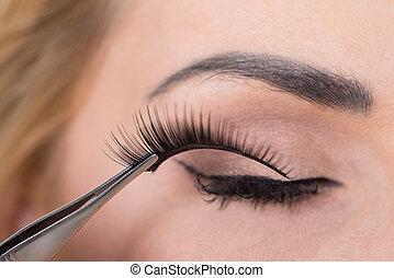 False Eyelashes Being Put On Woman's Eye - Close-up of false...