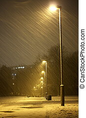 Snowy winter night - Row of lampposts in a snowy winter...