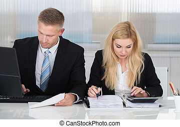 Business People With Paperwork At Desk In Office