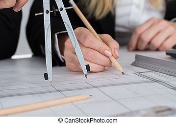 Architects Working On Blueprint At Desk In Office - Cropped...